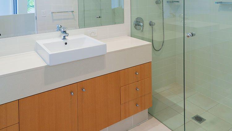 Una ducha a la altura del suelo y con mampara de cirstal es lo mejor para un baño pequeño