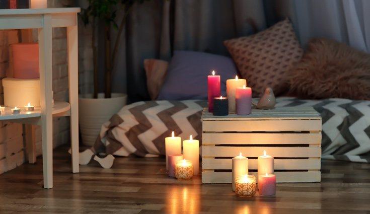 Habitación con velas de color blanco, lila, rosa y negro